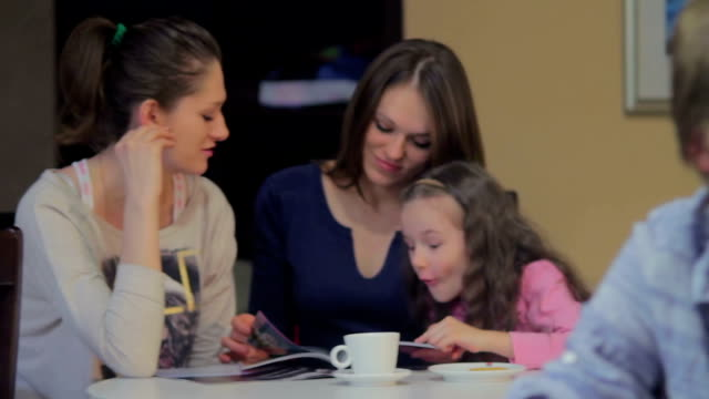 Visitors in cafe, happy mother chatting excited daughter, couple video