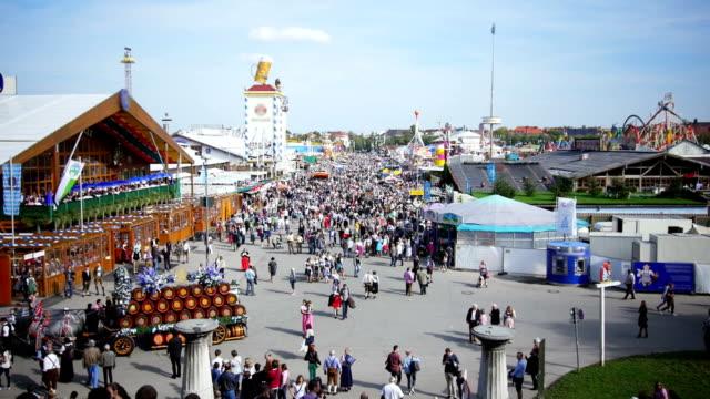 t/l visitors walking through oktoberfest fairgrounds - oktoberfest stock videos and b-roll footage