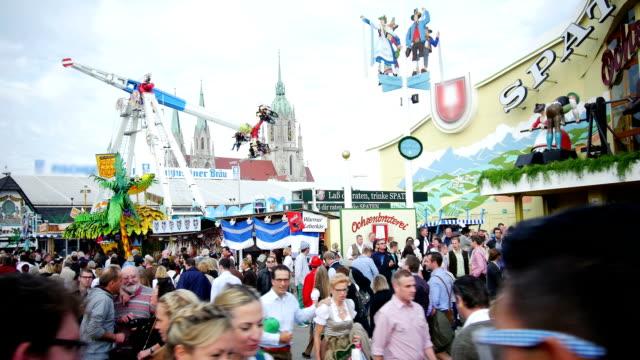 visitors walking through oktoberfest fairgrounds - oktoberfest stock videos and b-roll footage