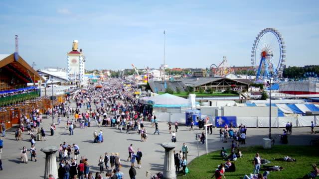 besucher zu fuß durch das oktoberfest fairgrounds (4 k uhd zu/hd) - volksfest stock-videos und b-roll-filmmaterial