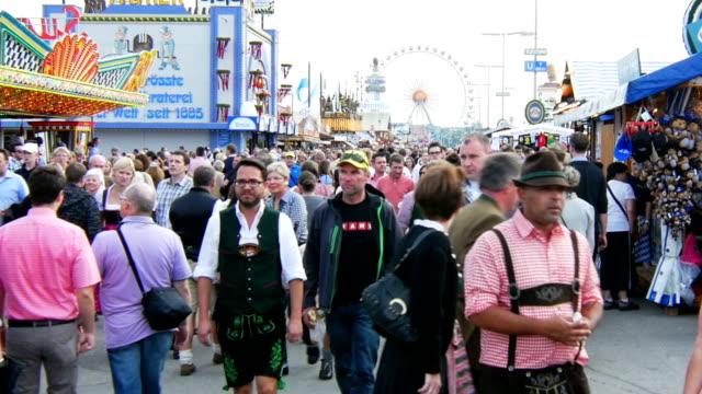 visitors walking through oktoberfest fairgrounds (4k/uhd to hd) - oktoberfest stock videos and b-roll footage