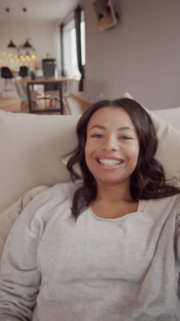vídeos de stock e filmes b-roll de vivacious mixed race woman lying on couch and video chatting - vertical