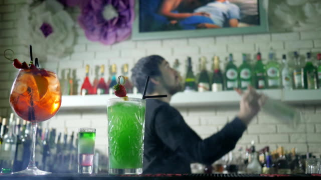 vivid alcoholic drink with fresh strawberries stand on bar table and on background of barkeeper performs juggle with bottles video