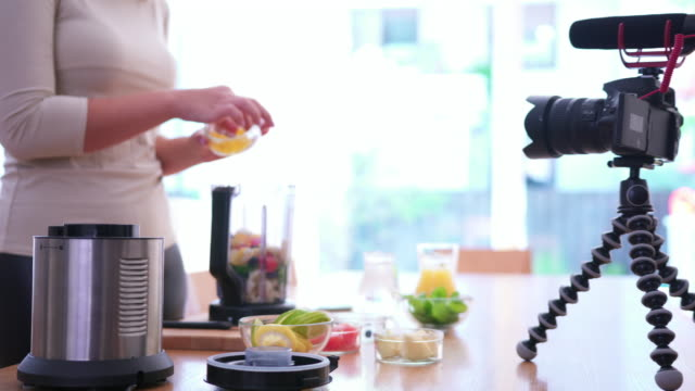 Vlogging Woman recording herself making a smoothie for her vlog citrus fruit videos stock videos & royalty-free footage