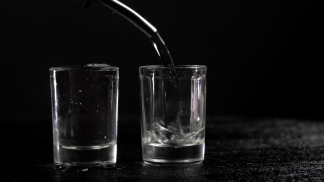 vídeos de stock e filmes b-roll de vodka is poured into two glasses on black background - rum bebida branca