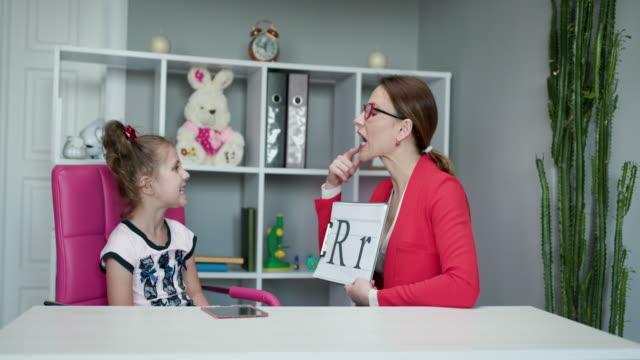 vidéos et rushes de voice ability problem speaking lesson concept. orthophoniste enseigne aux filles à dire la lettre r. femme orthophonothérapeute enseigner la prononciation préscolaire kid sound - professeur(e)