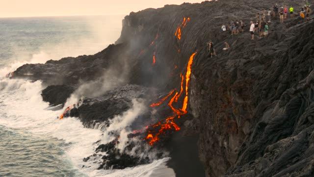 stockvideo's en b-roll-footage met vulkanische uitbarsting lava die in het water hawaï stroomt - geologie