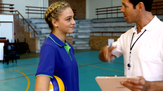Volleyball coach talking to teenage girl 4k video