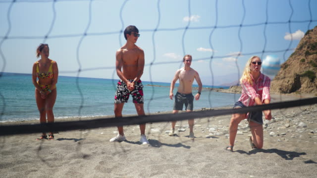 Volleyball Game at the Beach Young men and women playing volleyball on idyllic sandy beach. A man dives to the ground to hit the ball. beach volleyball stock videos & royalty-free footage