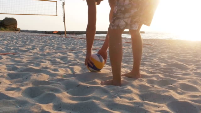 volleyball-spieler treten ball am strand, slow-motion - volleyball stock-videos und b-roll-filmmaterial