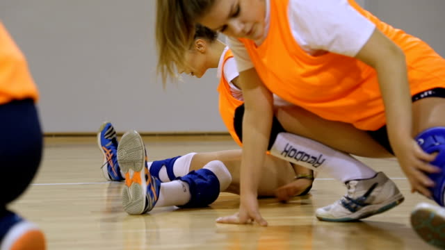 Volleyball players stretching Volleyball women players stretching before training. practice drill stock videos & royalty-free footage