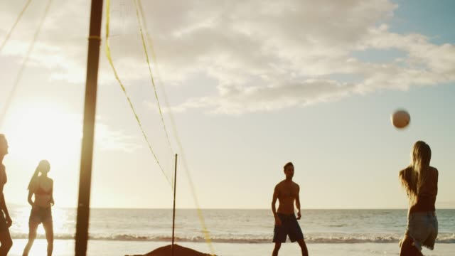 Volleyball rally in paradise at sunset Active friends playing beach volleyball at sunset, cinematic slow motion golden light volleyball sport stock videos & royalty-free footage