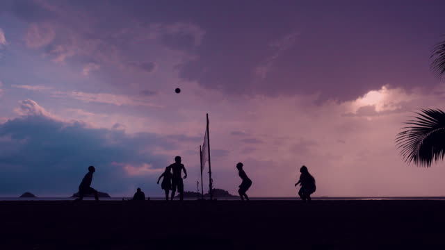 volleyball silhouette on sunset beach - volleyball stock videos and b-roll footage