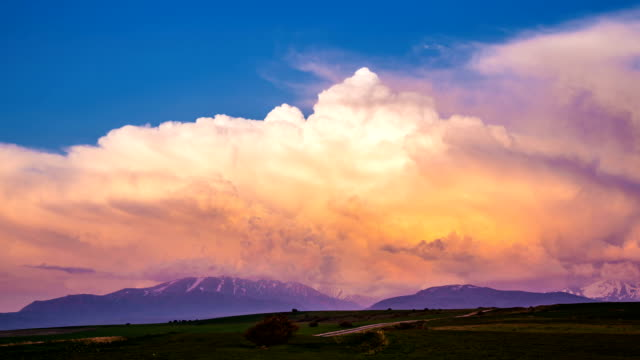 Volumetric colorful storm clouds swirl over the mountains. Timelaps video