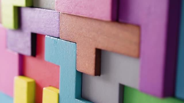 forme geometriche volumetriche, primo-up, dolly shot. blocchi di legno colorati. il concetto di pensiero logico. - a forma di blocco video stock e b–roll