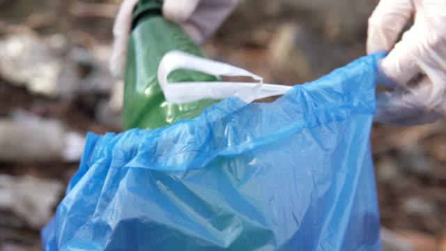vídeos de stock, filmes e b-roll de um voluntário coleta lixo em uma área florestal. ecologia do meio ambiente. - ecossistema