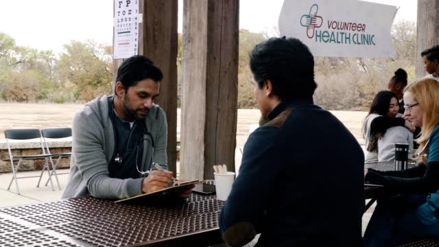 Volunteer doctor asks male patient questions during healthcare event Mid adult male doctor takes notes as a mid adult male patient discusses his symptoms. The doctor is volunteering at an outdoor free clinic in a public park. Doctors and patients are in the background. clipboard stock videos & royalty-free footage