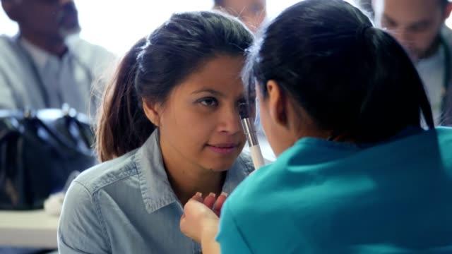vídeos de stock, filmes e b-roll de médico voluntário examina os olhos da mulher clínica médica - pré estreia