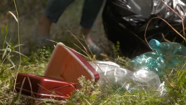vídeos y material grabado en eventos de stock de joven ecologista voluntaria recogiendo basura de plástico vieja en el bosque, recogiendo residuos, contaminación de la tierra, problema ambiental - animal joven