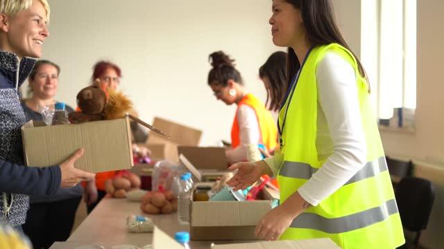 여성에게 기부 상자를 주는 자원봉사자 - giving tuesday 스톡 비디오 및 b-롤 화면