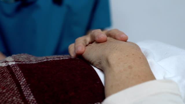 vídeos y material grabado en eventos de stock de voluntario sosteniendo la mano de una paciente envejecida acostada en la cama, cuidado y apoyo - geriatría