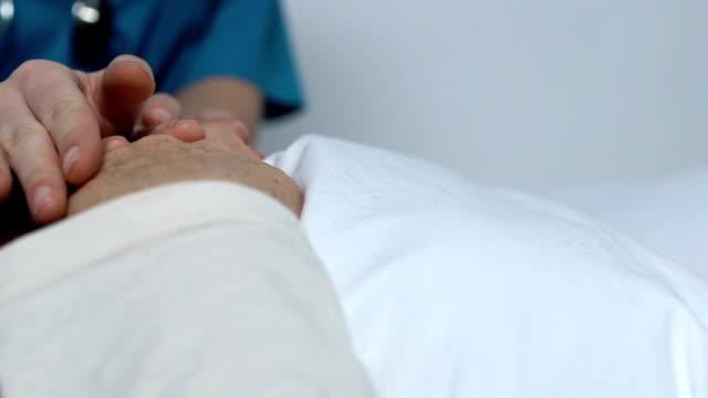 vídeos y material grabado en eventos de stock de voluntario sosteniendo las manos de la hembra que sufre cáncer apoyando después de la quimioterapia - geriatría