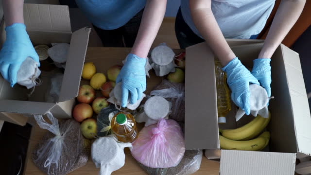 vídeos de stock e filmes b-roll de volunteer in protective suits pack products. food delivery services during coronavirus pandemic for working from home and social distancing. shopping online. - benefits