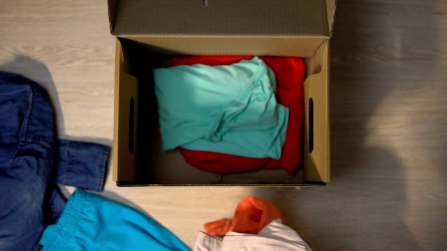 wolontariusz pakujący podarowane ubrania w kartonowym pudełku, pomagający sierocińcowi, charytatywni - odzież filmów i materiałów b-roll