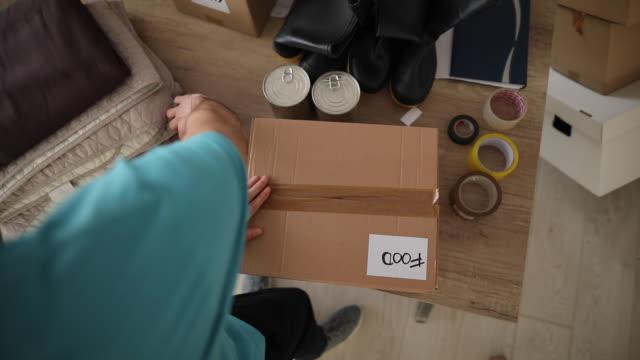 자선 푸드 뱅크에서 자원 봉사 포장 기부 상자 - giving tuesday 스톡 비디오 및 b-롤 화면