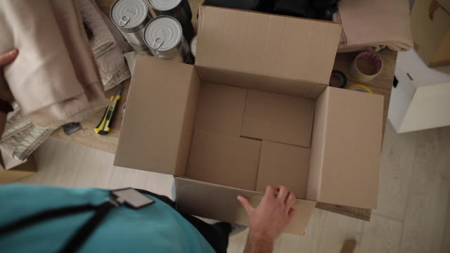 Volunteer packing donation boxes in charity food bank One man, volunteer packing donation boxes in charity food bank. giving tuesday stock videos & royalty-free footage