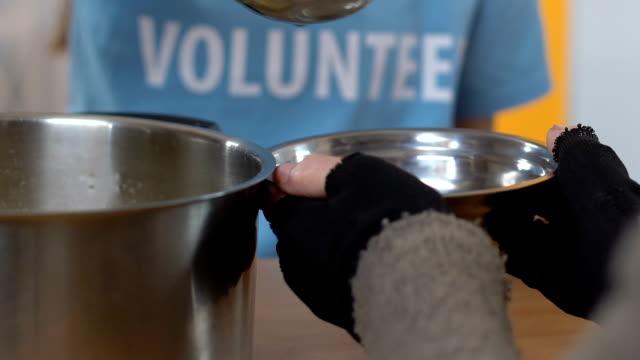 vídeos de stock e filmes b-roll de volunteer pouring soup for homeless person in social support center, assistance - benefits