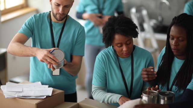 기부된 음식 및 기타 물품을 포장하는 자원봉사팀 - giving tuesday 스톡 비디오 및 b-롤 화면