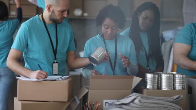 기부된 음식을 포장하는 자원봉사자 팀 - giving tuesday 스톡 비디오 및 b-롤 화면
