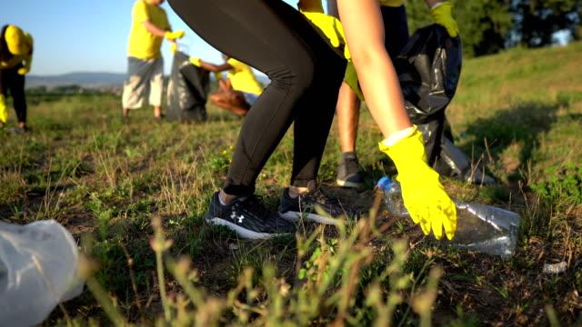 vídeos de stock e filmes b-roll de volunteer together pick up trash in the park - dedicação