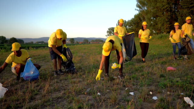 공원에서 쓰레기를 수거하는 자원봉사자 - 헌신 스톡 비디오 및 b-롤 화면