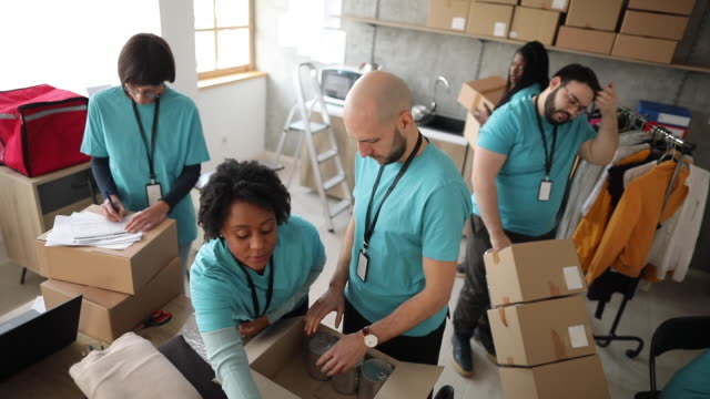 Volunteers checking and packing charitable donations A multi-ethnic group of young adults at a community service, preparing boxes with food and other goods donations giving tuesday stock videos & royalty-free footage