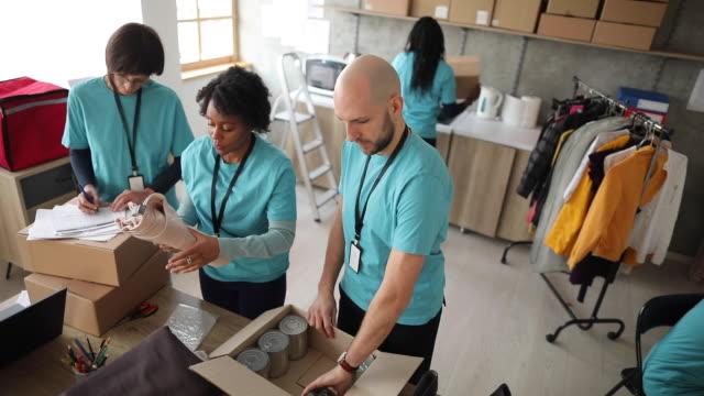 자선 기부를 확인하고 포장하는 자원봉사자들 - giving tuesday 스톡 비디오 및 b-롤 화면