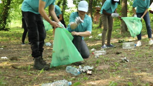 stockvideo's en b-roll-footage met vrijwilligers schoonmaken een openbaar park - eco