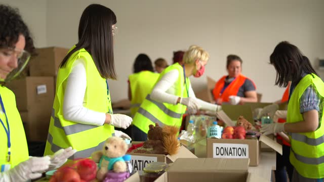 vídeos y material grabado en eventos de stock de voluntarios recogiendo donaciones de alimentos en almacén en tiempo de pandemia - food drive