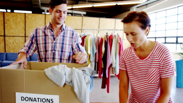 Volunteers going through donation box of clothes video