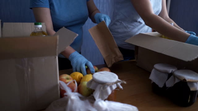 vídeos de stock e filmes b-roll de volunteers in protective suits pack products. food delivery services during coronavirus pandemic for working from home and social distancing. shopping online. - benefits