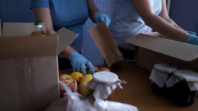 volontärer i skyddsdräkter packar produkter. livsmedelsleveranstjänster under koronaviruspandemi för arbete hemifrån och socialt avståndstagande. handla online. - välgörenhet bildbanksvideor och videomaterial från bakom kulisserna