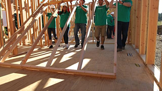 Volunteers lifting wall
