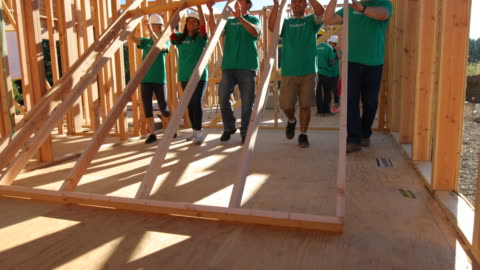 vídeos de stock e filmes b-roll de volunteers lifting wall - comunidade