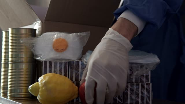 Volunteers pack food in a package for social assistance. Food delivery during quarantine. Self-isolation, pandemic concept. video