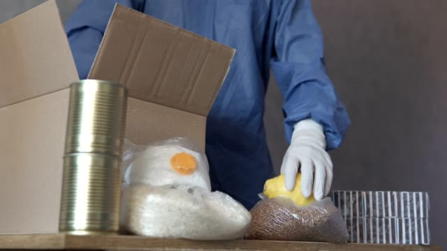 Volunteers pack food in a package for social assistance. Food delivery during quarantine. - vídeo