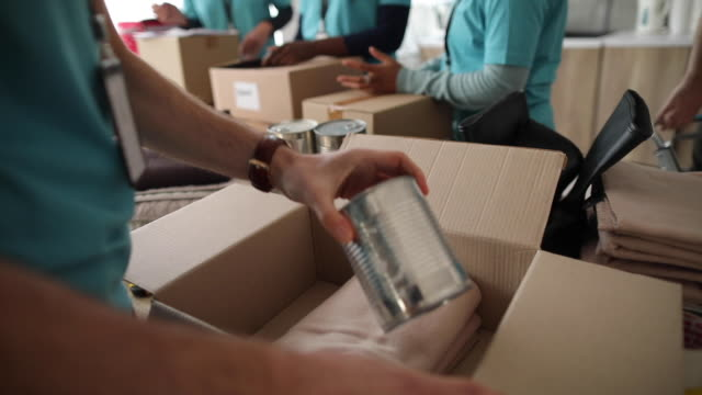 Video Volunteers packing donation boxes in charity food bank