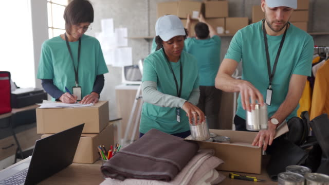 Volunteers packing humanitarian aid Group of multi-ethnic volunteers working in charitable foundation giving tuesday stock videos & royalty-free footage