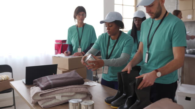 Volunteers packing humanitarian aid Group of multi-ethnic volunteers working in charitable foundation. Charity and relief work. giving tuesday stock videos & royalty-free footage