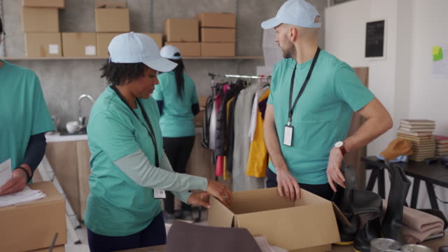 Volunteers packing humanitarian aid Group of multi-ethnic people working in charitable foundation giving tuesday stock videos & royalty-free footage
